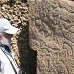 Turchia - Urfa (l'antica Edessa). Dario Seglie, Direttore del CeSMAP di Pinerolo, esamina una grande stele in pietra con figure animali (felini, uccelli, serpenti)  del tempio di Göbekli Tepe