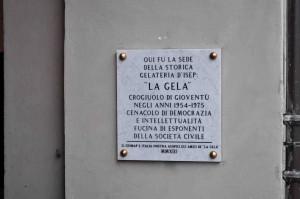 """La targa marmorea murata sotto i portici di Piazza Barbieri a Pinerolo, ricorda il luogo dove ebbe vita la Gelateria D'Isep, sede del gruppo di giovani Pinerolesi che, mezzo secolo or sono, la frequentarono assiduamente creando una coesa """"banda"""" giovanile ancora oggi esistente."""
